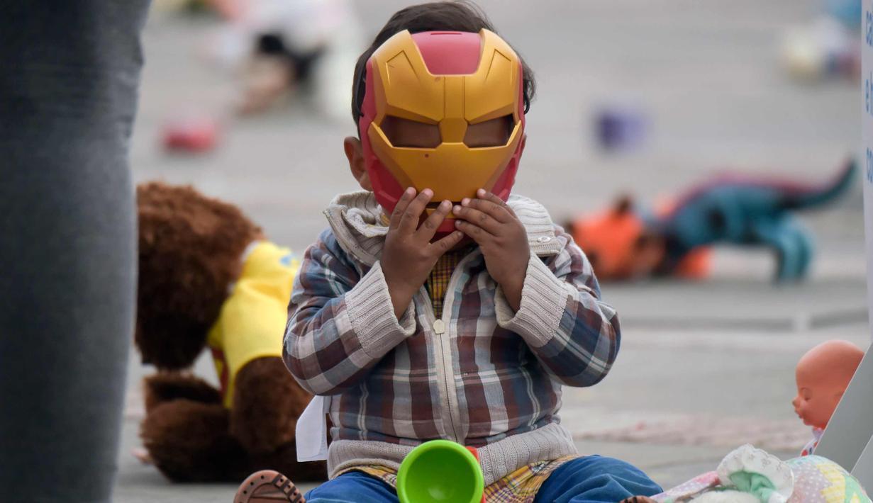 Seorang anak memakai topeng Iron Man saat ikut aksi di Alun-alun Bolivar, Bogota, Kolombia (20/11). Aksi ini memprotes penganiayaan terhadap anak sekaligus meningkatkan kesadaran akan tanggung jawab dalam perlindungan anak. (AFP Photo/Raul Arboleda)