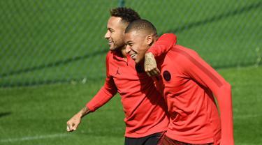 Pemain Paris Saint-Germain (PSG), Neymar (kiri) bercanda dengan Kylian Mbappe (kanan) saat sesi latihan di Paris Barat, Prancis, Senin (17/9). PSG akan menghadapi Liverpool di Liga Champions pada 19 September 2018. (FRANCK FIFE/AFP)