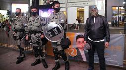 Seorang pria bertopeng Halloween berdiri di sebelah petugas polisi yang mengenakan pakaian anti huru hara di Hong Kong, Kamis (31/10/2019). Peraturan larangan penutup wajah dibuat untuk membantu memadamkan protes yang semakin memanas di bulan kelima. (AP Photo/Kin Cheung)