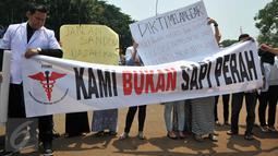 Puluhan dokter dari Pergerakan Dokter Muda Indonesia (PDMI) melakukan unjuk rasa di depan Istana Merdeka, Jakarta, Senin (7/9). Mereka  memprotes penyelenggaraan ujian kompetensi di berbagai universitas yang ada di Indonesia. (Liputan6.com/Gempur M Surya)