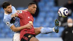 Striker Manchester United, Anthony Martial (kanan) berebut bola dengan bek Manchester City, Ruben Dias dalam laga lanjutan Liga Inggris 2020/21 di Etihad Stadium, Minggu (7/3/2021). MU menang 2-0 atas Mancity. (AFP/Peter Powell/Pool)