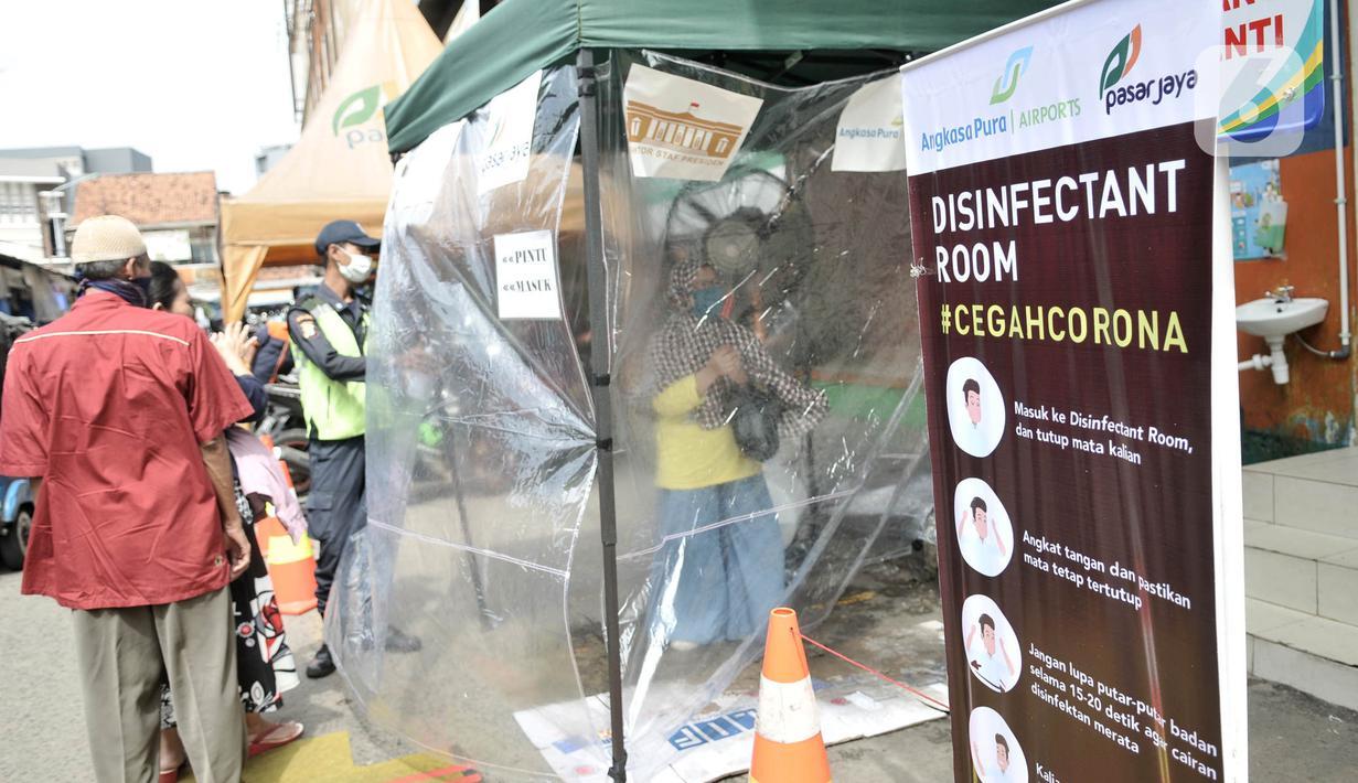 Pengunjung antre memasuki Ruang Disinfektan di Pasar Jatinegara, Jakarta, Kamis (26/3/2020). Pemerintah menyediakan Ruang Disinfektan yang dikhususkan untuk memeriksa serta mensterilisasi pengunjung guna mencegah penyebaran Covid-19 di tempat keramaian. (merdeka.com/Iqbal S. Nugroho)