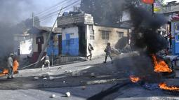 Ban terbakar setelah dibakar oleh pengunjuk rasa yang kesal dengan meningkatnya kekerasan di lingkungan Lalue, Port-au-Prince, Haiti, Rabu (14/7/2021). Presiden Haiti Jovenel Moise dibunuh pada 7 Juli. (AP Photo/Matias Delacroix)
