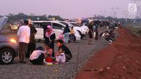 Pemudik menyantap hidangan berbuka puasa di pinggir Tol Fungsional Pemalang-Batang, Jawa Tengah, Minggu (10/6). Sambil berbuka mereka juga mendinginkan kendaraannya. (Liputan6.com/Arya Manggala)