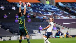 Kiper Arsenal Emiliano Martinez berusaha menangkap bola tembakan striker Tottenham Hotspur, Harry Kane pada pertandingan lanjutan Liga Inggris di Stadion Tottenham Hotspur di London, Inggris, Minggu (12/7/2020). Tottenham menang tipis atas Arsenal 2-1. (Michael Regan/Pool via AP)