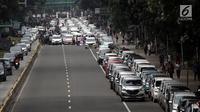 Suasana saat ratusan sopir taksi online memarkir mobilnya di Jalan Medan Merdeka Barat, Jakarta, Rabu (14/2). Para pengemudi menolak Permenhub Nomor 108 karena dianggap memberatkan. (Liputan6.com/Arya Manggala)