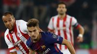 Pemain Barcelona, Denis Suarez berebut bola dengan pemain Olympiakos, Vadis Odjidja-Ofoe pada laga babak penyisihan Grup D Liga Champions di Georgios Karaiskáki, Rabu (1/11). Barcelona hanya mampu bermain imbang dengan skor 0-0. (AP/Thanassis Stavrakis)