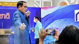 Perdana Menteri (PM) Thailand, Prayuth Chan-ocha menyemprotkan pembersih tangan ke barisan depan wartawan dalam konferensi pers di Bangkok, Selasa (9/3/2021). Hal Itu dilakukan Prayuth dalam upaya untuk menghindari pertanyaan tentang perombakan kabinet. (HO/ROYAL THAI GOVERNMENT/AFP)