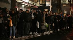 Para pengguna komuter antre menunggu bus di dekat stasiun kereta bawah tanah Charing Cross, London, Senin (9/1). Aksi mogok para pekerja kereta bawah tanah London mengakibatkan kekacauan di hampir semua stasiun. (Daniel Leal-Olivas/AFP)