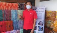Holib, 49 tahun, Ketua Kelompok Usaha Tenun Sutera Alam Mardian Putera, Tasikmalaya tengah menunjukan ragam motif kain sutera kelompoknya, dari suntikan modal CSR Pertamina. (Liputan6.com/Jayadi Supriadin)