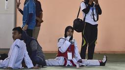 Peserta perempuan melakukan pemanasan sebelum bertanding pada Kejuaraan Terbuka Taekwondo di Banda Aceh (17/7/2019). Kejuaraan Taekwondo ini berlangsung 12-18 Juli 2019. (AFP Photo/Chaideer Mahyuddin)