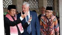 """Mike Pence berbincang dengan Imam Besar Nasaruddin Umar di Masjid Istiqlal, Jakarta (20/4). Pence memuji kultur Islam moderat di Indonesia sebagai """"inspirasi"""" pada awal kunjungannya di negara berpenduduk mayoritas Muslim. (AFP Photo / Pool / Adi Weda)"""