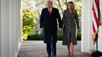 Presiden AS Donald Trump dan Ibu Negara Melania Trump melewati barisan tiang untuk Thanksgiving turkey pardon tahunan di Rose Garden Gedung Putih di Washington, DC pada 24 November 2020. (MANDEL NGAN / AFP)