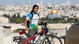 Pria Taiwan, Jacky Chen, berpose dengan sepedanya di Bukit Zaitun yang menghadap ke Kota Tua Yerusalem dan Kubah Batu pada 10 Juni 2019. Chen memulai misinya bersepeda keliling dunia sejak 2015 dan telah singgah di 64 negara dengan menempuh perjalanan sejauh 54.000 km. (MENAHEM KAHANA/AFP)