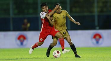 Pemain Persija Jakarta, Sandi Sute (kiri) berebut bola dengan pemain Bhayangkara Solo FC, TM Ichsan, pada laga Piala Menpora 2021 di Stadion Kanjuruhan, Malang, Rabu (31/3/2021). (Bola.com/M Iqbal Ichsan)