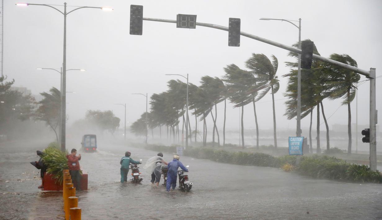 Pengendara motor menerjang hujan dan angin kencang yang dibawa Topan Mangkhut di Manila, Filipina (15/9). Topan Mangkhut menghantam pantai timur laut Filipina pada Sabtu pagi menghancurkan sebagian wilayah di negara tersebut. (AP Photo/Bullit Marquez)