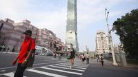 Warga memakai masker untuk melindungi dari penyebaran COVID-19 saat melewati Gedung Taipei 101 di Taipei, Taiwan, Sabtu (15/5/2021). Taiwan yang membuat iri dalam menahan COVID-19 memberlakukan pembatasan baru di ibu kota saat memerangi wabah terburuk sejak pandemi. (AP Photo/Chiang Ying-ying)