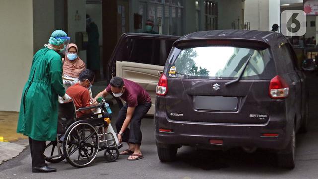 Petugas medis (kiri) mendorong pasien yang duduk di kursi roda di IGD RSUD Cengkareng, Jakarta, Rabu (23/6/2021). Meningkatnya kasus COVID-19 di Jakarta membuat pasien harus mengantre di luar IGD untuk mendapatkan tempat perawatan. (Liputan6.com/Herman Zakharia)