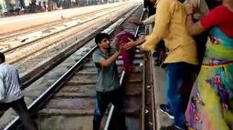 Gambar dari video pada 20 November 2018, seorang pria India menggendong bayi dan memberikan kepada ibunya  setelah terjatuh di samping rel di stasiun kereta api di Mathura, Uttar Pradesh. Bayi satu tahun itu selamat tanpa luka sedikitpun. (NNIS / AFP)