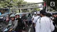 Peserta aksi reuni 212 berjalan saat kendaraan terjebak kemacetan di kawasan Jalan Thamrin dan Merdeka Barat, Jakarta, Senin (2/12/2019). Sejumlah ruas jalan di Jakarta mengalami kemacetan parah akibat aksi reuni 212 di kawasan Monas. (Liputan6.com/Faizal Fanani)