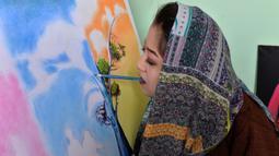 Foto yang diambil pada 5 Desember 2019 menunjukkan seniman Robaba Mohammadi melukis menggunakan mulut di studionya di Kabul. Untuk membuktikan bahwa stigma negatif tentang perempuan dan disabilitas salah, Robaba mengembangkan bakat di bidang seni lukis. (NOORULLAH SHIRZADA/AFP)
