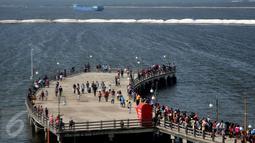 Pengunjung berada di dermaga cinta untuk menikmati suasana angin laut di Ancol, Jakarta, Sabtu (18/7/2015). Wisata pantai Ancol masih menjadi pilihan favorit warga Jakarta untuk mengisi libur lebaran kedua ini bersama keluarga. (Liputan6.com/JohanTallo)