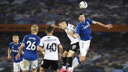Bek Everton, Michael Keane, berebut bola atas dengan penyerang Salford City, Ashley Hunter, pada laga Piala Inggris di Stadion Goodison Park, Kamis (17/9/2020) dini hari WIB. Everton menang 3-0 atas Salford City. (AFP/Peter Powell/pool)