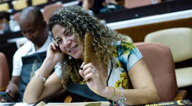 Peserta wanita menunjukkan cerutu yang dibuatnya selama kelas master dalam Festival Havana Cigar ke-20 di Istana Konvensi di Havana, Kuba (28/2). (AFP Photo/Adalberto Roque)