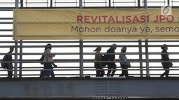 Pejalan kaki melintas di JPO Jalan Sudirman yang dipasangkan Spanduk peringatan revitalisasi, Jakarta (6/11). Tiga JPO yang akan direvitalisasi JPO Bundaran Senayan, JPO Polda Metro Jaya, dan JPO di Stadion Utama GBK. (Liputan6.com/Immanuel Antonius)