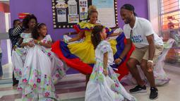Mantan pesebak bola dunia Didier Drogba menari bersama anak-anak saat melakukan acara amal organisasi internasional Peace and Sport, di Cartagena, Kolombia (19/3). (Cesar Carrion/Colombian Presidency/AFP)