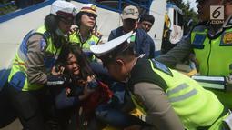Petugas polisi berusaha mengamankan seorang wanita saat terjadi aksi demo di Jalan Medan Merdeka Barat, Jakarta, Rabu (28/3). Para driver taksi online ini menuntut Permenhub Nomor 108 Tahun 2017 dicabut. (Merdeka.com/Imam Buhori)
