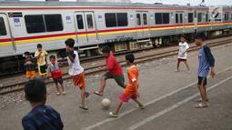 Kereta melintas di kawasan Kemayoran, Jakarta, Senin (24/7). Minimnya lahan bermain menyebabkan anak-anak terpaksa bermain di lokasi tersebut, meskipun berbahaya bagi keselamatan. (Liputan6.com/Immanuel Antonius)