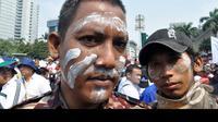 Para pendemo ini sengaja mengoleskan pasta gigi di wajahnya untuk meminimalisir efek pedas gas air mata, Jakarta, Kamis (21/8/2014)  (Liputan6.com/Miftahul Hayat)