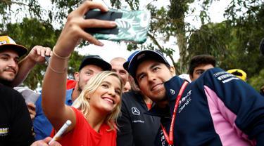 Pembalap F1 Racing Point, Sergio Perez berselfie dengan penggemarnya saat tiba di Sirkuit Melbourne Grand Prix di Melbourne, Jumat (15/3). Seri GP Australia akan menjadi pembuka ajang Formula 1 (F1) musim 2019. (Reuters/Edgar Su)