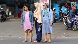 Momen ketika biarawati bergandeng tangan dengan wanita berkerudung saat menyeberangi jalan di kawasan Lenteng Agung, Jakarta, Rabu (18/4). Keharmonisan keduanya dapat menjadi contoh bagi masyarakat dalam menjaga kedamaian. (Liputan6.com/Immanuel Antonius)