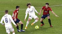 Gelandang Real Madrid, Luka Modric, berusaha melewati pemain Osasuna pada laga Liga Spanyol di Stadion El Sadar, Sabtu (9/1/2021). Kedua tim bermain imbang 0-0. (AP/Alvaro Barrientos)