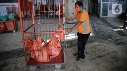 Pekerja membawa paket dan logistik yang akan didistribusikan di Sentral Pengolahan PT Pos Indonesia (Persero), Jakarta, Jumat (15/5/2020). Pengiriman paket via Pos pada H-9 Lebaran 2020 mencapai 1,8 juta barang atau naik 20 persen dibandingkan periode sama tahun lalu. (Liputan6.com/Faizal Fanani)