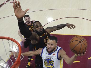 Aksi pemain Warriors, Stephen Curry melakukan tembakan saat diadang pemain Cavaliers, LeBron James pada gim ketiga final NBA basketball di Quicken Loans Arena, (6/6/2018). Warriors kalahkan Cavaliers 110-102. (Gregory Shamus/Pool via AP)