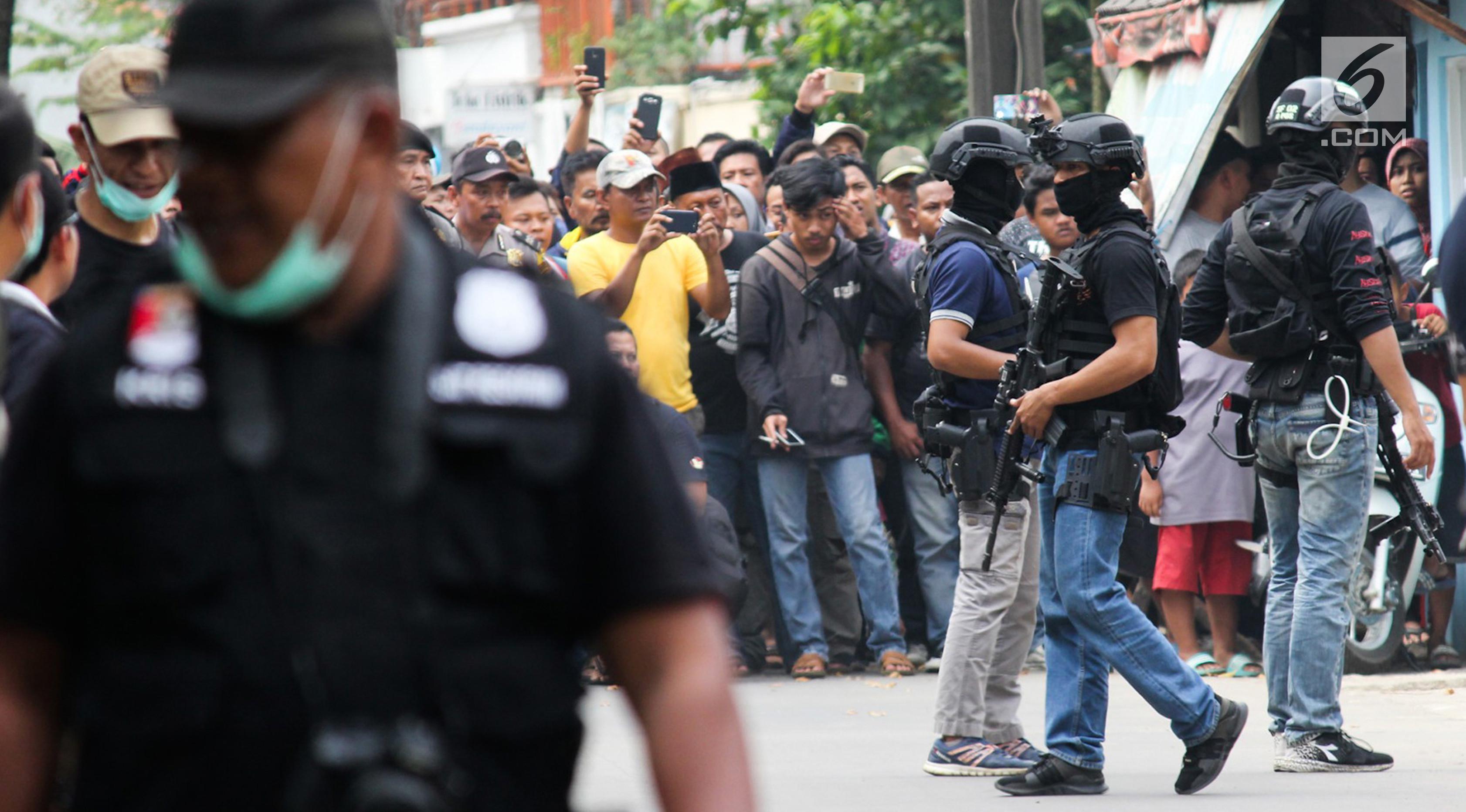 Warga antusias menyaksikan penggerebekan terduga teroris oleh Densus 88 Antiteror Mabes Polri di Jalan Gempol Raya, Kunciran Indah, Tangerang, Banten, Rabu (16/5). Warga dilarang mendekati lokasi saat penggerebekan terjadi. (Merdeka.com/Istimewa)