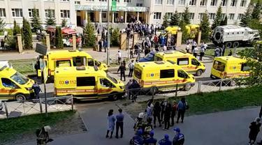 Ambulans dan truk polisi diparkir di sebuah sekolah setelah penembakan, di Kazan, Rusia, Selasa, 11 Mei 2021. Media Rusia melaporkan bahwa beberapa orang telah tewas dan terluka dalam penembakan di sekolah tersebut. (AP Photo)