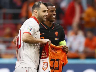 Belanda diwakili kapten mereka, Georginio Wijnaldum memberikan penghormatan berupa jersey yang bertuliskan Pandev dan bernomor punggung 122 seusai pertandingan antara Makedonia Utara melawan Belanda di Grup C Piala Eropa 2020. (Foto: AFP/Pool/Koen van Weel)