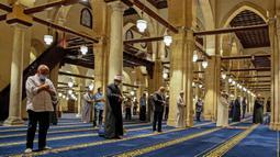 Umat Muslim melaksanakan salat tarawih dengan menerapkan jaga jarak selama bulan Ramadan di Masjid al-Azhar, Kairo, Minggu (17/5/2020). Bagi umat Islam di seluruh dunia menjalankan ibadah puasa tahun ini di tengah pembatasan akibat corona Covid-19 adalah yang pertama kalinya. (Samer ABDALLAH/AFP)