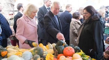 Pangeran Charles bersama istrinya, Duchess of Cornwall Camilla berbincang dengan pedagang ketika mengunjungi Swiss Cottage Farmers Market di London utara, Rabu (6/11/2019). Kunjungan Charles dan Camila untuk memperingati ulang tahun ke-20 pasar tersebut. (Eddie Mulholland / POOL / AFP)