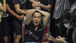 """Para pengunjuk rasa mengikat seorang pria yang diduga mata-mata China saat demonstrasi di Bandara di Hong Kong (13/8/2019). Para Demonstran menduga pria yang mengenakan kaus bertuliskan """"I love polisi"""" ini merupakan penyusup yang dikirim pemerintah China. (AP Photo/Vincent Yu)"""