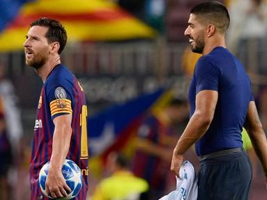 Pemain Barcelona, Lionel Messi dan rekan setimnya, Luis Suarez meninggalkan lapangan usai laga grup B Liga Champions melawan PSV Eindhoven di Camp Nou, Selasa (18/9). Hattrick Messi mewarnai kemenangan telak 4-0 Barcelona atas PSV. (AFP/Josep LAGO)