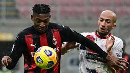 Striker AC Milan, Rafael Leao (kiri) berebut bola dengan gelandang Crotone, Ahmed Benali dalam laga lanjutan Liga Italia 2020/21 pekan ke-21 di San Siro Stadium, Milan, Minggu (7/2/2021). AC Milan menang 4-0 atas Crotone. (AFP/Miguel Medina)
