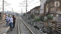 Sejumlah pelajar berjalan menyusuri perlintasan kereta di Kampung Muka, Ancol, Jakarta, Selasa (5/11/2019). Pemprov DKI Jakarta mengusulkan anggaran konsultan penataan kampung kumuh sebesar Rp 556 juta per rukun warga (RW) pada rancangan APBD 2020. (Liputan6.com/Herman Zakharia)