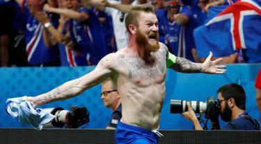 Kapten timnas Islandia, Aron Gunnarsson melakukan selebrasi dengan melepaskan jersey usai menyingkirkan Inggris di babak 16 besar Piala Eropa 2016, Selasa (28/6) dini hari. Inggris takluk 1-2 meski sempat unggul terlebih dahulu. (REUTERS/Michael Dalder)