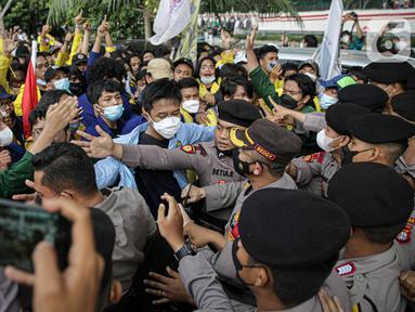 Mahasiswa yang tergabung dalam Aliansi BEM Seluruh Indonesia (BEM SI) saling dorong dengan polisi saat menggelar aksi di sekitar Gedung Merah Putih KPK, Jakarta, Senin (27/9/2021). Polisi menahan mahasiswa untuk merangsek maju. (Liputan6.com/Faizal Fanani)