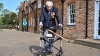 Veteran Perang Dunia II Kapten Tom Moore (99) berjalan di kebunnya di Marston Moretaine, London, 16 April 2020. Moore mengumpulkan donasi lebih dari 16 juta dolar untuk National Health Service (NHS) dengan berjalan 100 kali bolak-balik jarak 25 meter di taman belakang rumahnya. (Justin TALLIS/AFP)